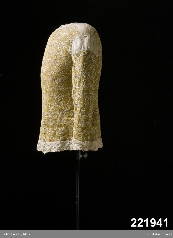 Tröja av  gult silke slätstickad med instickade  mönster i aviga maskor i form av svängda tulpaner med konturer av vitt garn, de aviga maskorna inne i mönstret är i silke omspunnnet med guldtråd. Nederkanten rutstickad med det vita garnet. Vitt även i ärmkant, kring halsen och på ärmkullen. Tröjan stickad i 5 delar, stickad fram och tillbaka, inte runt. Det vita garnet bildar långa flotteringar på avigan. Det vita garnet kan möjligen ha varit ljusblått från början såsom är fallet med den tröja, nu i Victoria&Albert museum, som är mycket lik denna, se V&A id. 807-1904. Tröjan har sytts ihop fram men har ursprungligen varit helt öppen och haft någon form av knäppning, troligen i likhet med den engelska med tätt sittande kulknappar i trådarbete. I nederkant finns fragment av ett rött lacksigill. Utländsk tillverkning. Se Gunnel Hazelius-Berg: Stickad tröja. Fataburen 1941 sid 211 /Berit Eldvik 2011-12-07