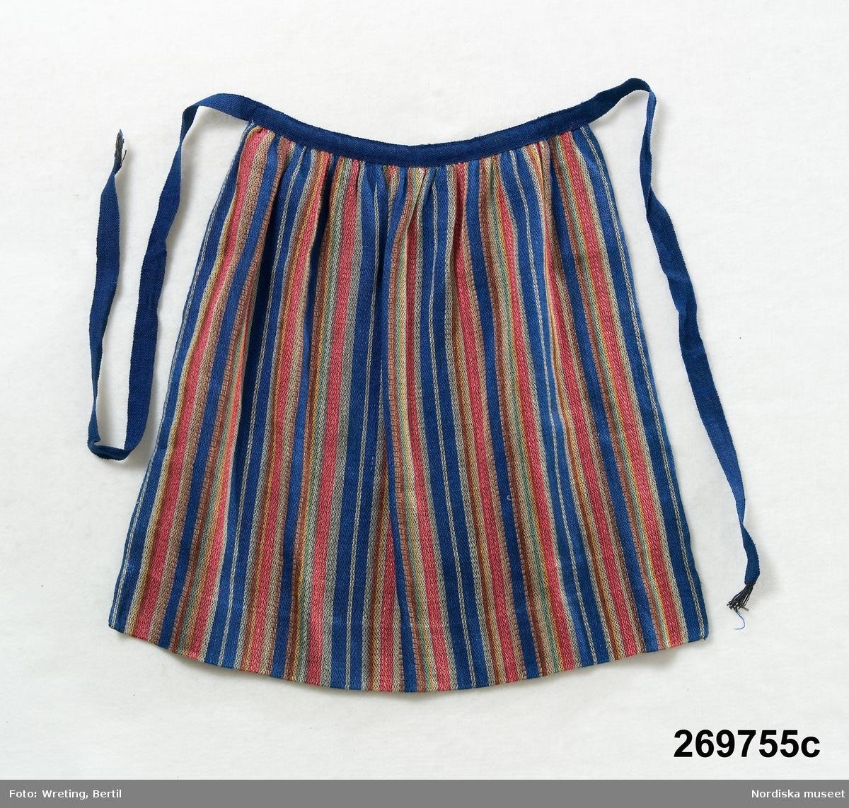 Danderydsdräkt för flicka konstruerad 1955, bestående av 4 delar. a. Kjol b. Livstycke c. Förkläde d. Överdel  a. Kjol i halvylle med varp av svart bomullsgarn och inslag av svart ullgarn och blått  lingarn, sydd i 2 våder, veckad mot bred linning, 24 cm bred fåll. b. Livstycke av rött spetskyprat linne, foder av vit bomullssatin, 2 par knappar av silver i form av 5-bladig blomma sammanhållna med kedjelänkar. c. Förkläde halvlinne med svart bomullsvarp och randigt inslag av lingarn i blått, gult, rött, grått och brunt.Linneing och knytband av blått ylle, 5 cm bred fåll. d. Överdel av vit linnelärft med snibbskuren krage, knäppning fram med 4 par tryckknappar, stråveck. Ärmar vidsydda med ärmspjäll, knäppt ärmlinning kantad med smal knypplad spets.  Buren av Calill Randall-Edström, hennes systrar Camilla och Cisela hade  likadana sydda av modern Carola Randall- Edström som var ordförande i sockendräktskommittén som 1955 konstruerade dräkten. För vuxen kvinna finns även en mössa  som är inspirerad av Kristina Banérs mössa (1600-t) .på en porträttmålning som hänger på Djursholms slott.  Foton från 1955 på flickorna i sina dräkter se kapsel i folioformat med Folkdräktsrörelsen: Uppland, Danderyd.  Berit Eldvik juli 2005