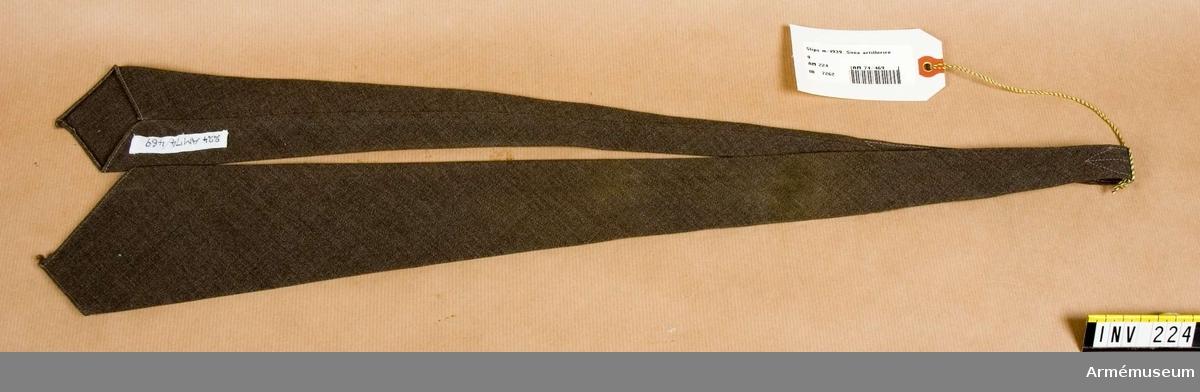Av gråbrungrönt tyg, avsedd att knytas för hand. Tyget är taget på snedden. Söm och extra maskinstickning 200 mm mitt bak.