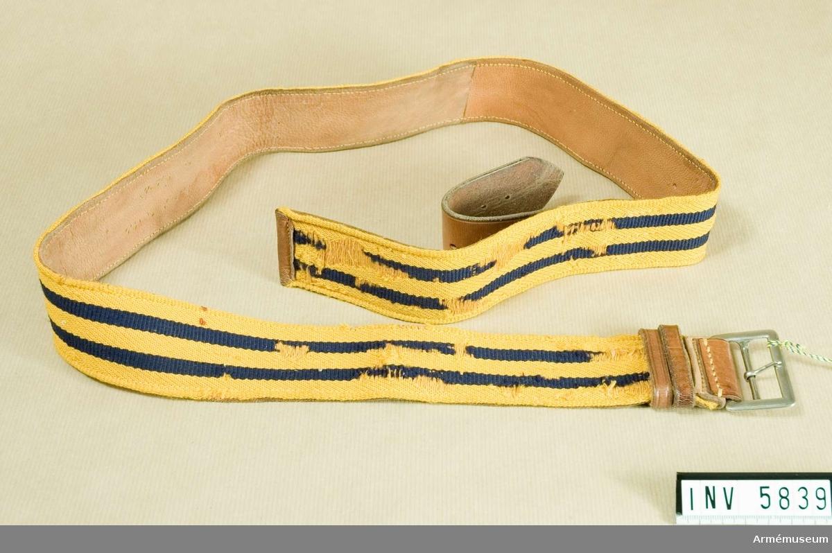 Kypertvävt gult ylleband med två mörkblå ripsränder, vardera 7 mm breda. Skärpet är fodrat med ljust skinn, och knäpps med ett vitmetallspänne. En lädertamp, 170 mm lång, som är påstickad på fodret, knäpps och spänns med metallspännet. Själva yllebandet täcker spännet och lädertampen och fästs tillsammans med denna i en lädersölja.  Fastställt genom generalorder 21 november 1931 nr 2506.