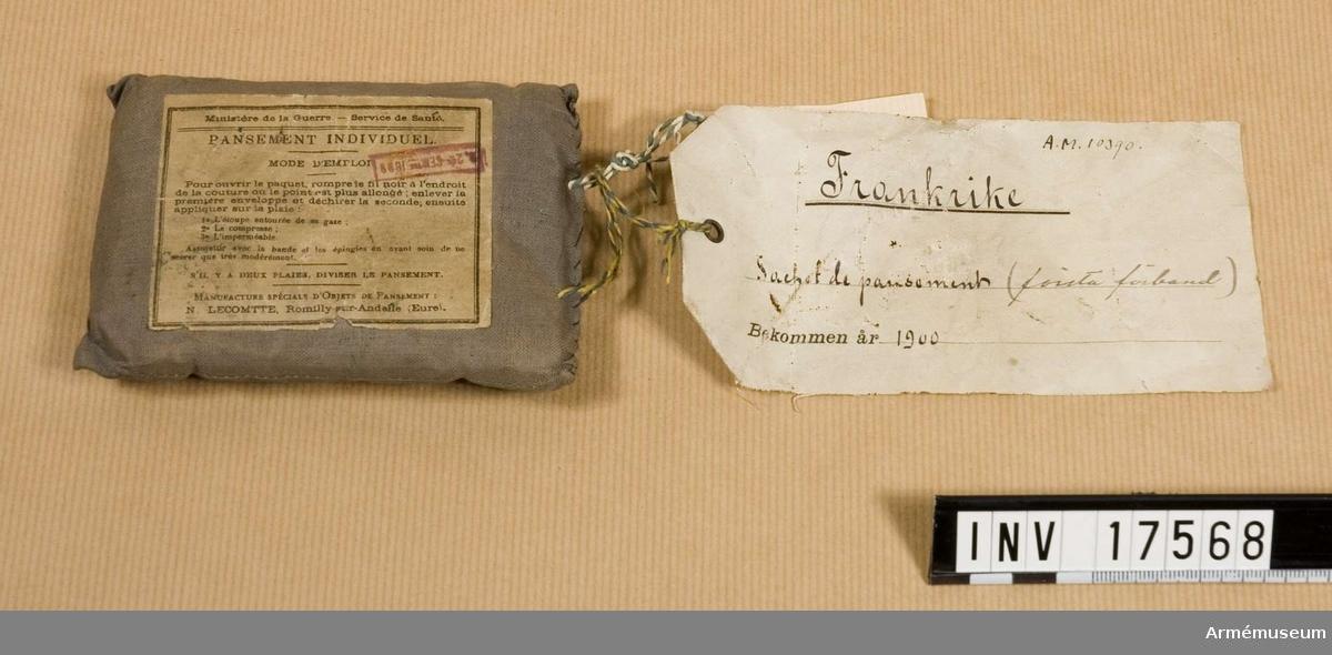 """Grupp C II.  Första förband, Frankrike. Första förbandspaket fyrkantigt av grått bomullstyg, 12 cm långt och 8.5 cm brett.  På paketet är klistrat en  pappersetikett med påskrift och stämpel: 1) """"Ministere de la Guerre - Service de Sant - Pansement individuel"""" (Krigsministerium - Medicinalstyrelsen - Personligt förband) 2) stämpel: """"24 sept. 1898"""" Enligt etiketten innehåller paketet: 1) vadd med gasbinda 2) kompress och 3) vaxduk.  Paketet har en pappersetikett med påskriften: Frankrike, Cachet de pansoments"""" (första förband). Bekommen år 1900./Enligt kapten W. Granberg."""