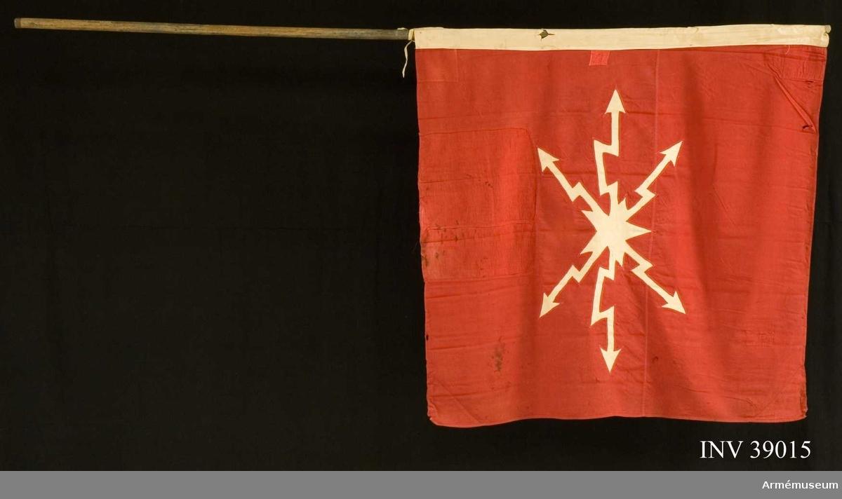 Grupp H III.   Rött, kypertvävt bottentyg med infällt vitt kompanimärke; Fälttelegrafkårens vingförsedda.  Duken har en vit strumpa vilken kan påföras stången. Maskinsydda lagningar. Duken har bristningar.  Samhörande nummer AM.039015-AM.039016.  Annat nr FM 76.