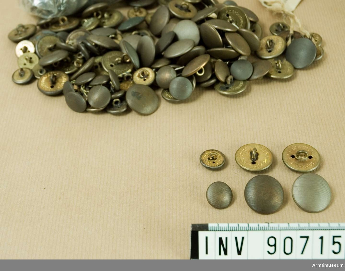 Större antal bronsfärgade, räfflade knappar. Både små och stora.