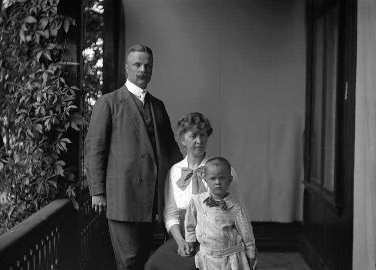 Tre personer står på en veranda, bakom dem är ett skynke upphängt som bakgrund. Personerna på bilden är Karl och Elisabeth Möller samt en av deras söner. Familjen Möller tillbringade många somrar på Gustafsberg och Elisabeth var även där som barn.