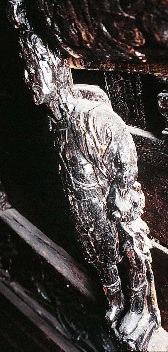 """Skulptur föreställande en mansfigur med ett långsmalt och skäggigt ansikte, under en hög, slät hjälm med stora plymer. Runt hjälmen är en stålkrona trädd. Bakom huvudet skymtar ett snäckskal. Figuren är iförd en rikt ornerad rustning av thoraxmodell. Utefter figurens rygg hänger en mantel, som också draperar den vänstra axeln.  Hela figuren är frontalt framställd. Höger arm hålls lätt böjd utefter sidan, med handen fattande om ett svärdsfäste. Vänster arm är något böjd rakt ut från sidan, och handen verkar fatta tag om manteln. Kroppstyngden är jämnt fördelad på båda benen.  Figuren står på en sockel, vilken pryds av en bred och grimaserande maskaron. Sockeln är även försedd med en banderoll som tycks helt slät och utan namninskription.  Upptill är bakstycket framdraget i en kraftig """"huvudplatta"""". Skulpturens baksida uppvisar tre snedställda, olika djupt liggande fält. Fälten, som utgör anliggningsytor, ger skulpturen en trappstegsformad profil. Huvudplattan är delvis skadad. Svärdets klinga saknas. I övrigt är skulpturen relativt välbevarad.  Text in English: A sculpture representing a male figure with a long and narrow face that is bearded and has a moustache. On the head there is a plumed helmet on which a crown with points has been placed and behind the head a large sea shell. The figure is wearing richly decorated thorax type armour. The mantle is hanging down the back and draped over the left shoulder.  The figure faces towards the front. The right arm is slightly bent and held at the side and the hand holds a sword hilt. The left arm is slightly bent and held out from the side and the left hand seems to hold the mantle. The weight of the body is carried on both legs.  The figure stands on a plinth with a broad and grimacing mask and also has a label which is quite smooth and without any inscription.  The upper part of the back extends obliquely upwards in a powerful """"head board"""". The sculpture''s back has three obliquely placed surfaces of different depths th"""