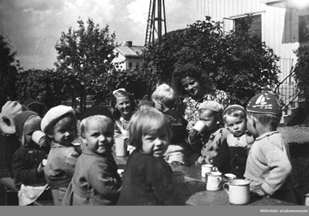 Lärare och barn fikar i trädgården vid Krokslätts daghem, Dalhemsgatan 7 i Krokslätt. Praktikant Margit Emilsson (gift Wannerberg -52) står vid barnen. Under Margits praktik som biträde 1945-10-01 - 1946-08-01.