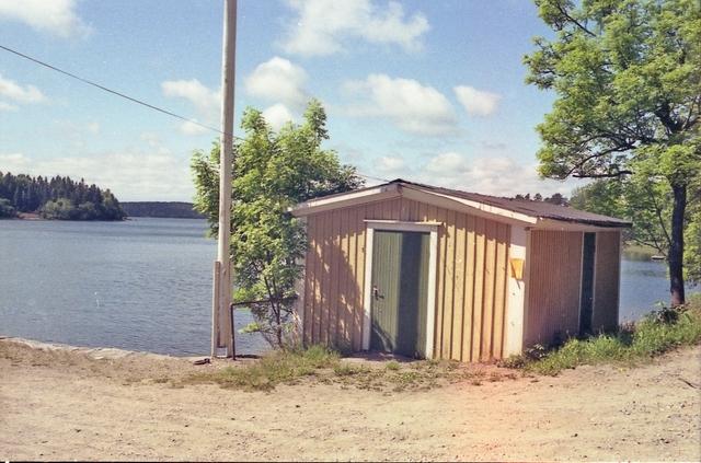 Entrédörren till sommarpostkontoret Barnens ö. (Ej i verksamhet på bilden). I verksamhet sista gången 1989. Trots nedlagd verksamhet är postkontoret ännu inte officiellt indraget 1990. Glesbygdspostställe till 1985.