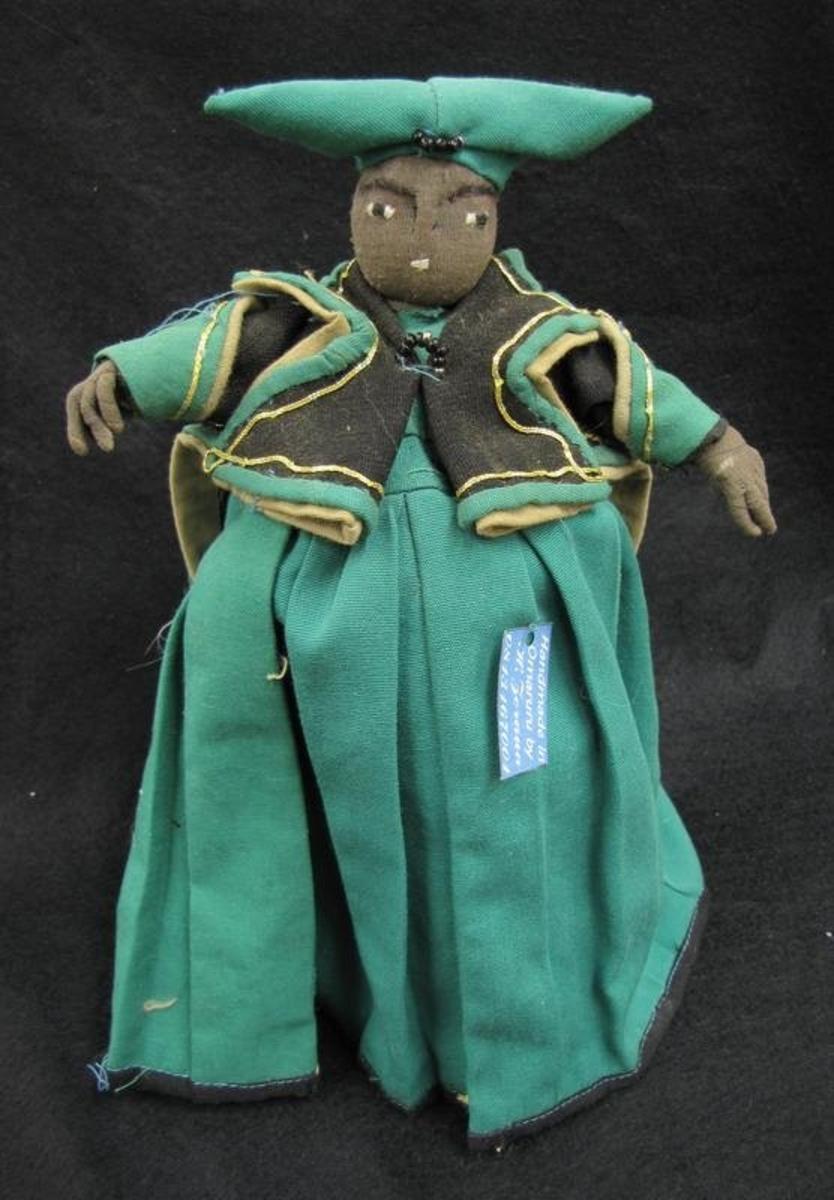 Docka i traditionell Hererodräkt. Sydd i grönt tyg med beiga och svarta detaljer. Västen har även guldfärgade band. På huvudet bärs en trekantig huvudbonad i grönt.   Dräkt för de hereros som lyder under Mbanderu nation. Gruppen samlas under den gröna flaggan, ''Green Flag'' och firar vid två högtider, i juni och augusti. Den liknande dräkten,  27 923, bärs av Chief Zerauas hustru, men och skiljer sig då den har en grön kjol och en svart väst. Ibland kallas gruppen även för Grön, vit och svart där färgerna representerar grönt för det grönskande gräset, vit t för fred och svart för sorg.   Dräkten är inspirerad av de victorianska kläder som bars av europeiska kvinnor i Namibia under 1800-talets andra hälft. Huvudbonaden skall symbolisera kreaturshorn då kreatren varit en viktig näring för hereros.   Dockan ingår i en samling av sex, 27 923-27 928. Dockan är tillverkad i Omaruru, Namibia, 2012 av Hildegard Zeraua, tillhörande The Royal House of Zeraua.