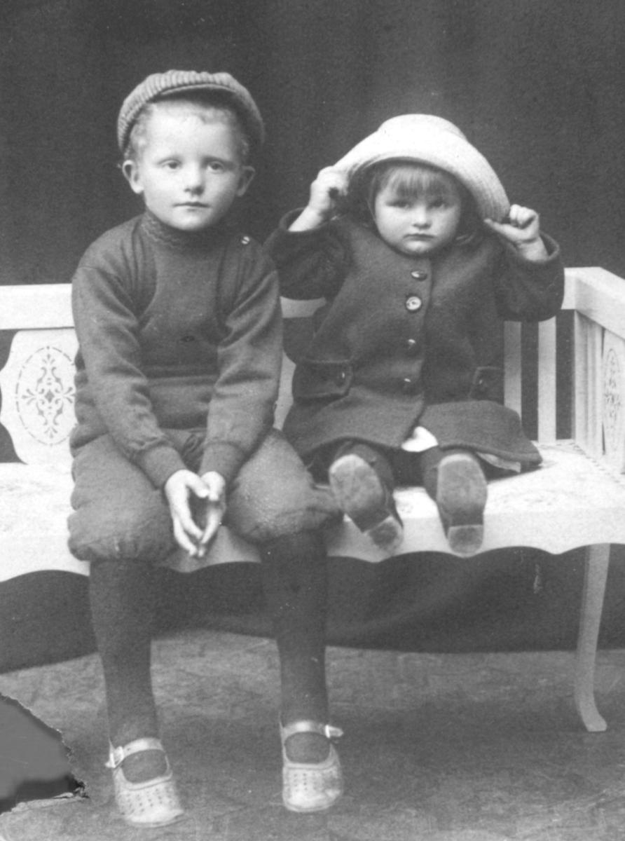 Portrett av Knut Evanger, og Gjertrud Evanger. De sitter på en hvit benk. Han er kledt i en genser, og kortbukser. På hodet har han en skyggelue. Sko med hvite reimer har han på bena. Gjertrud er kledt i en mørk kåpe med store svarte knapper. På hodet har hun en lys hatt som hun holder i. Hun har også sko på seg