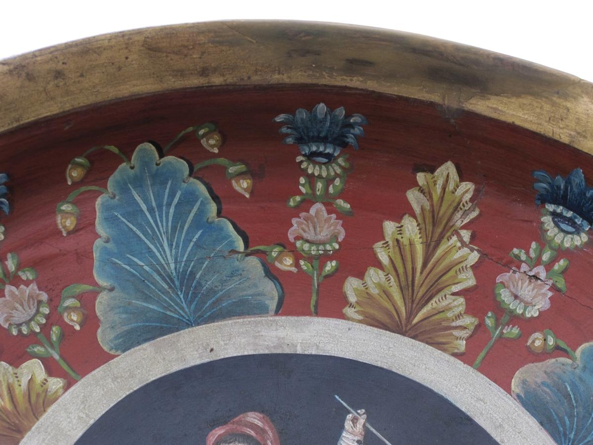 Innvendig rosemalt: stående mann med olkrus i sølv  i den ene hånd og lang krittpipe i den annen,  gule knebukser, blå knestrømper, hvit skjorte,  rød vest med sølje og hvit overfrakk, rød topplue,  grønt gress og mørkeblå bakgrunn. Langs kanten  grovmalt bord av avvekslende blå og gule flikede  blad med blå og rosa blomsterstengel imellom.