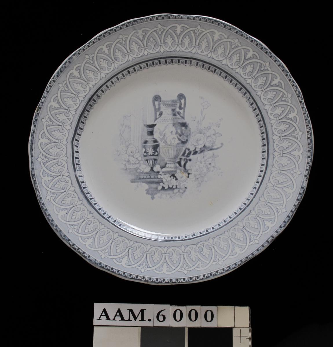 Stor og en mindre urne,/ et stettefat og rosenkvister./ gråblå bord