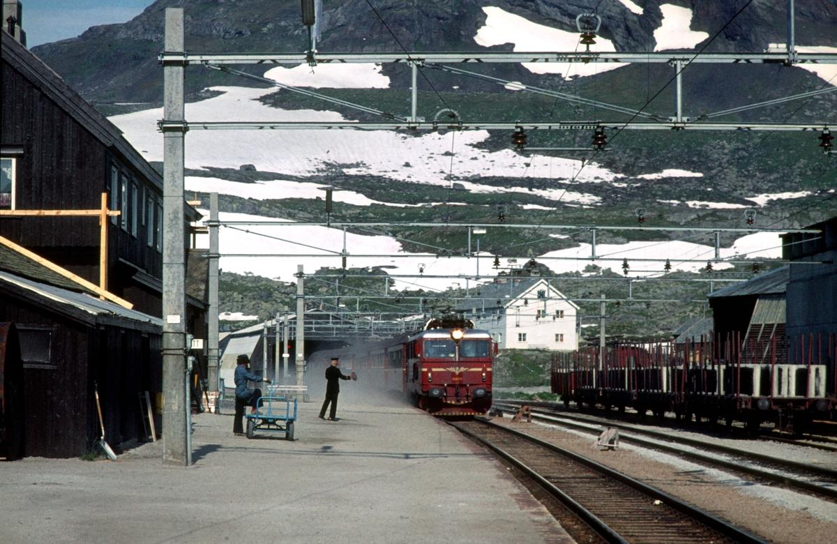 "Bergensbanen. Ekspresstog 62 Bergen - Oslo Ø passerer Finse stasjon. Lokomotiv type El 14. Togekspeditøren viser signal ""Kryssende tog har kommet""."