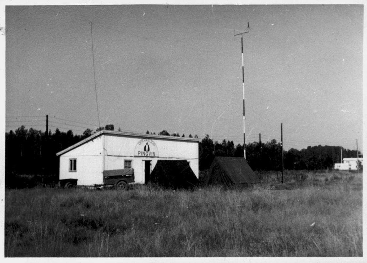 Bygning med med skilt over døren hvor det står skrevet Operasjon Pingvin. En radiomast ved bygningen.