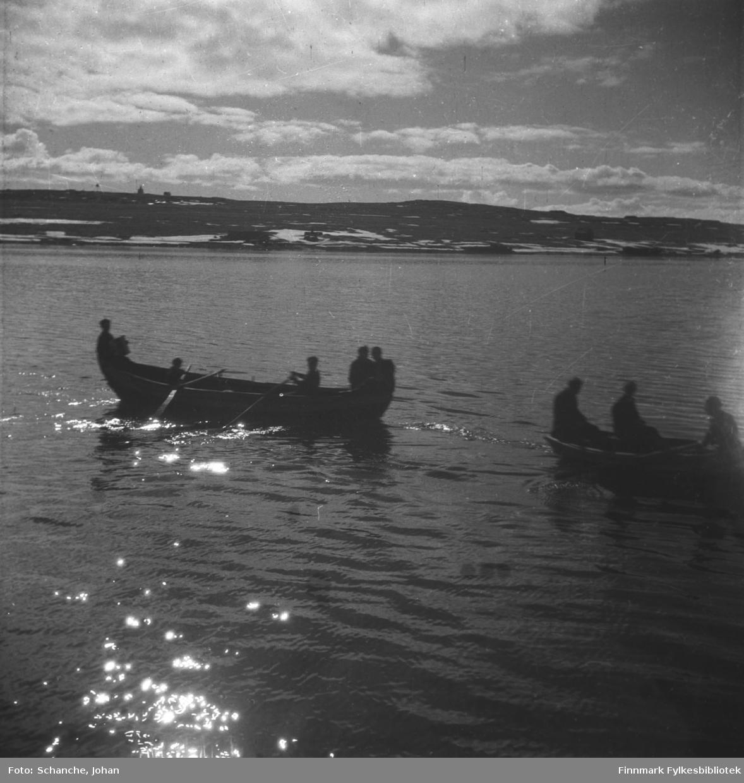 To robåter ligger i Varangerfjorden utenfør Vadsø -46.  To menn ror mot land. Båtene er fotografert mot sol slik at både båtene og menneskene om bord blir mørke siluetter i havet.  Det er litt snø på fjellet.