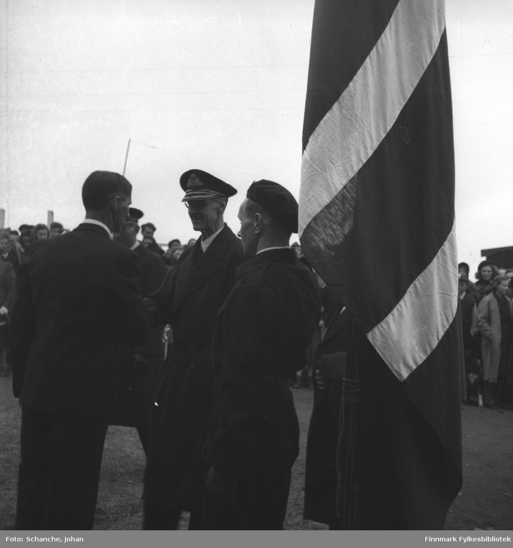 Kongebesøk:  Kong Haakon VII kommer til den kommunale lunsjen i Frelsesarmeens lokale og blir hilset velkommen av ordfører Bjarne Pedersen.  Bildet er litt uskarp.