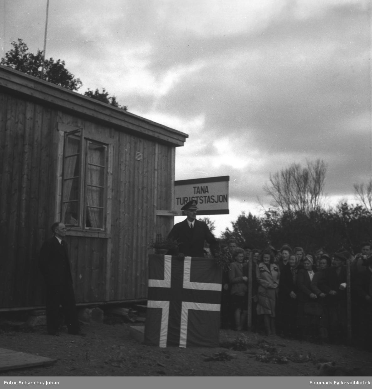 Kongebesøk i 1946:  Kong Haakon VII besøker Tana. Kongen står på talerplattformen ved Tana Turiststasjon og holder tale til folk som har samlet seg bak en gjerde like ved. Talerstolen er dekorert med flagg. Selve turiststasjonen er en nybygdt brakke.
