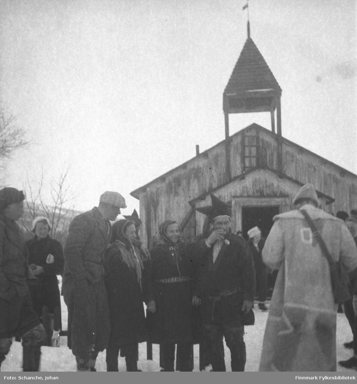 Polmak kirke fotografert på påsken -46. Mennesker, en del av dem i samedrakt, står utenfor kirkan. Gruppe av fire mennesker, to kvinner og to mann, ser på mann i lang skinnjakke som fotograferer?. Dette er trolig en vielse.