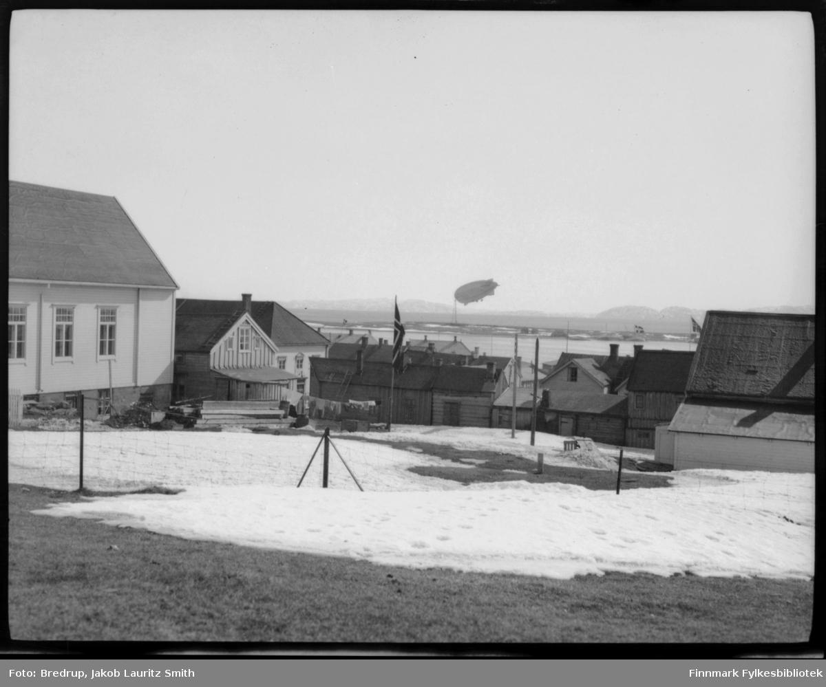 Dette er antakelig luftskipet Norge forankret ved luftskipsmasta på Vadsøya.  Bildet er tatt mellom bygninger i Vadsø fra samme vinkel som FBib.98012-016, som vi gjetter er tatt under Italias besøk i 1928.  Det ligger mye snø og man flagger i byen