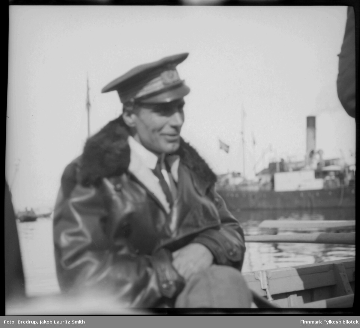 Portrett av en smilende Umberto Nobile som fraktes i robåt over sundet melleom Vadsøya og fastlandet.  Det var offisiell lunsj for offiserene i fylkesmannboligen, og Nobile var antakelig til stede.  I bakgrunnen ser vi et dampskip.