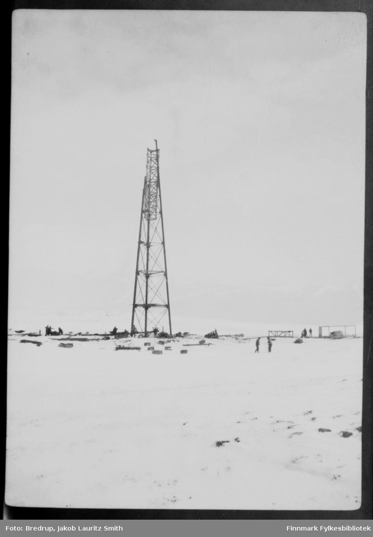 Arbeidere ved luftskipsmasta på Vadsøya.  Masta er nesten ferdig, bare toppen mangler.  Bildet må være tatt i perioden februar-begynnelsen av mai 1926.