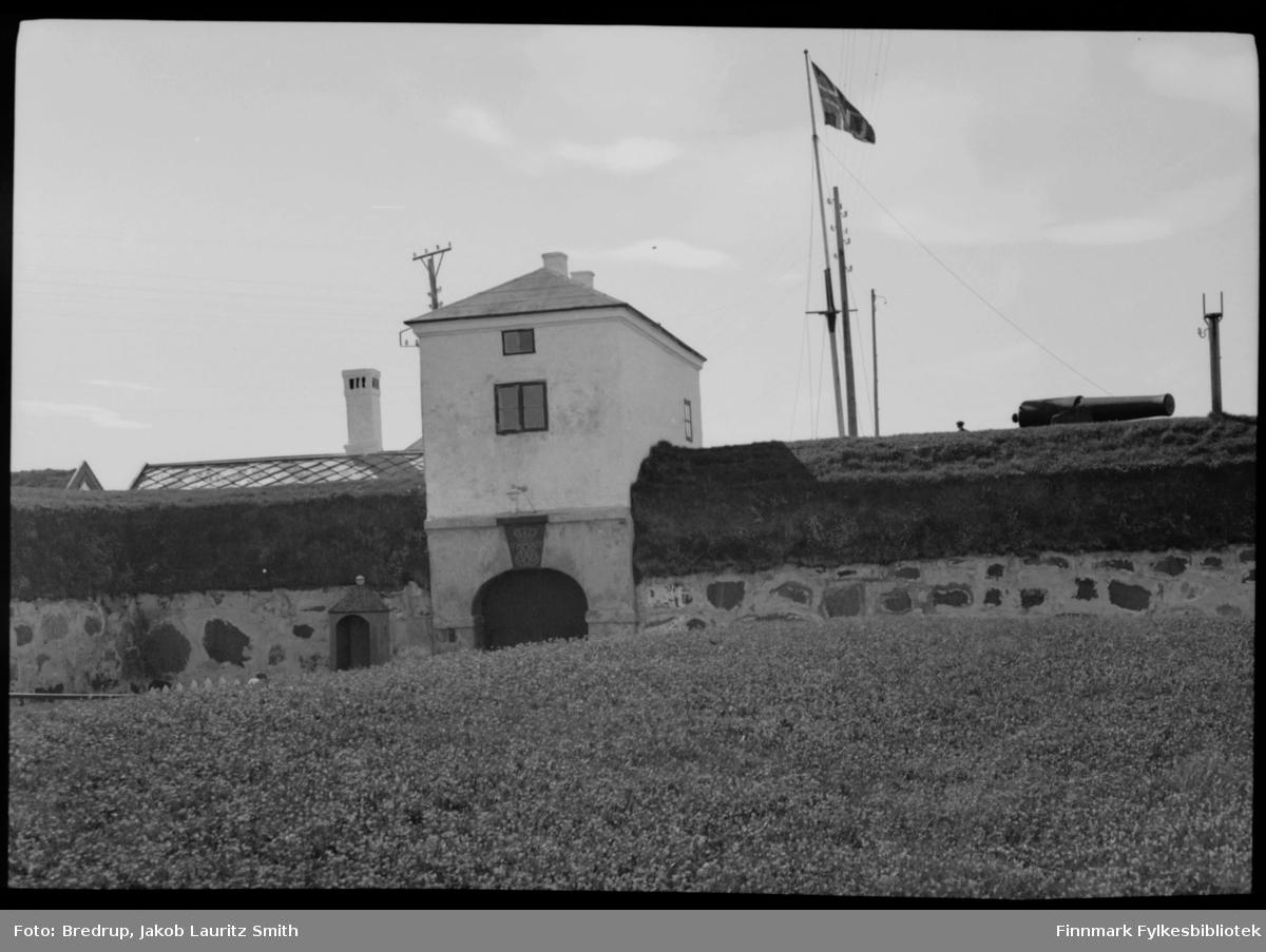Vardøhus festning fotografert mot porttårnet.  Bildet viser festningsvollene, en kanon oppe på vollene, det flagges i den spesielle bardunerte flaggstanga på festninga.