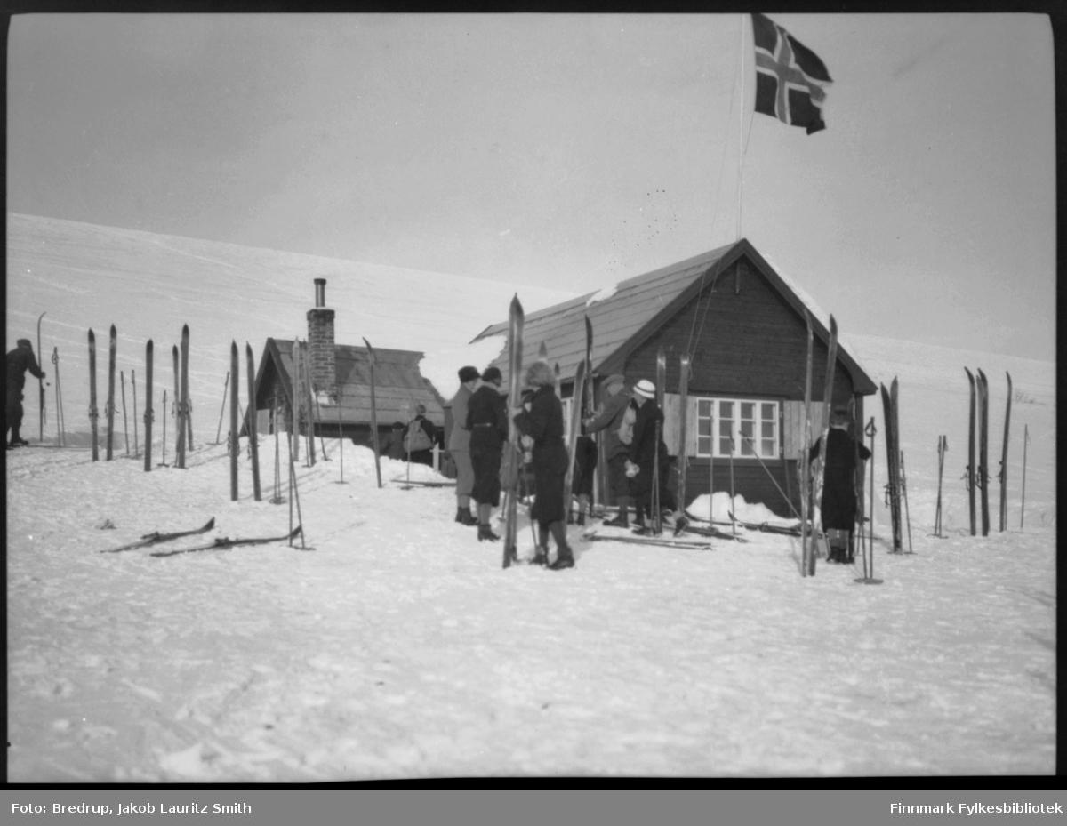 Bilde tatt utenfor skihytta i Viinika.  En skog av ski utenfor hytta, noen folk står og prater med hverandre.  Flagget er heist.