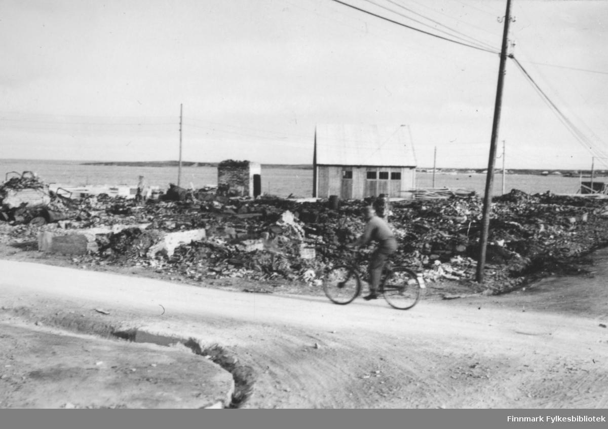 Ruiner i Vadsø sentrum etter andre verdenskrig. I forgrunnen en vei og en mann som sykler der. Til høyre for ham står det en stolpe. I bakgrunnen er det en tomt med ruiner, en liten bygning, og bak der igjen ser man havet