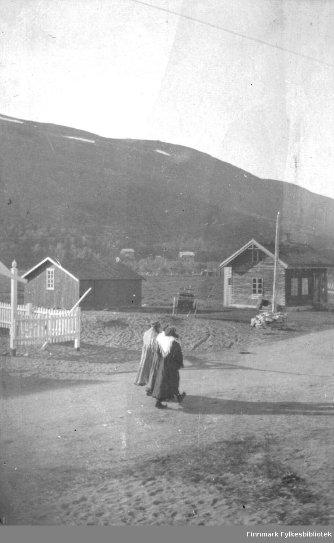 To samiske konfirmanter passerer kirka på Langnes. Bildet viser også to bygninger og i bakgrunnen Tanaelva.