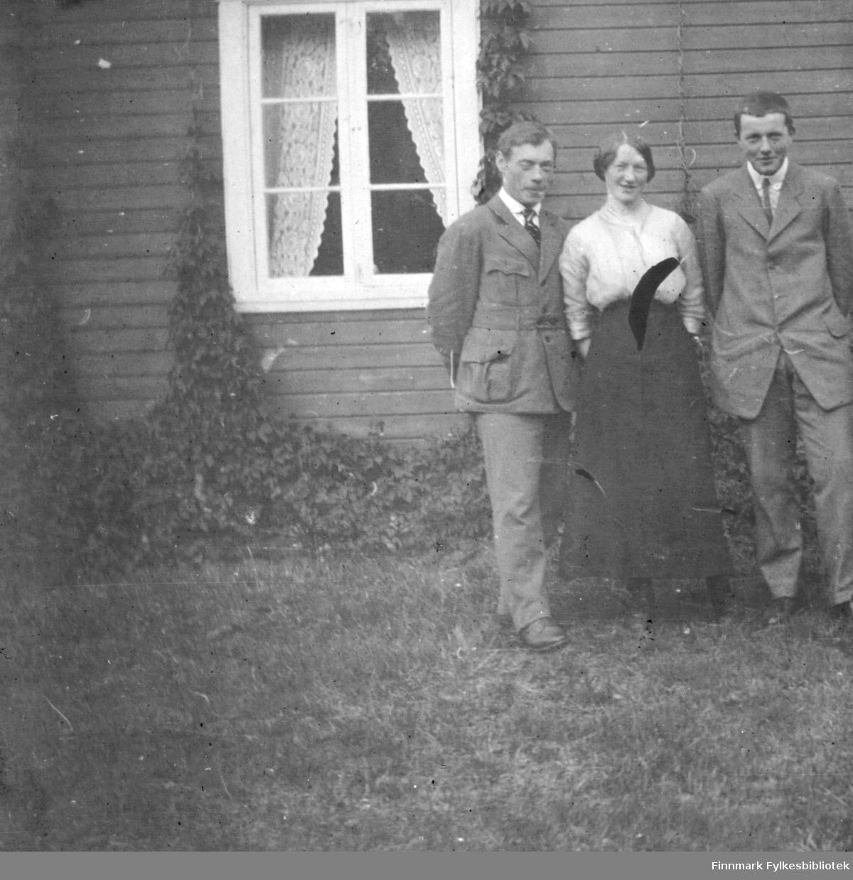 En dame og to menn fotografert utenfor et hus i Rassejåkka i Tana.