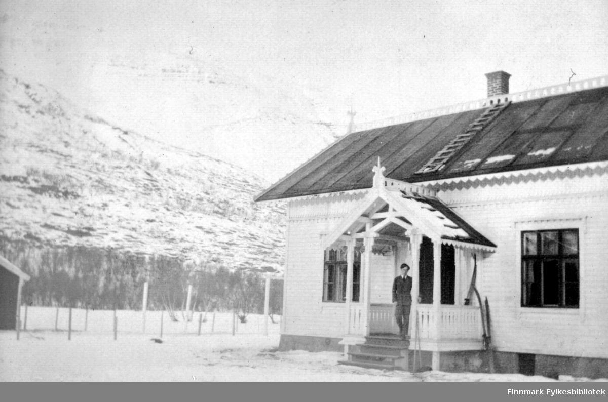 Hans Gabrielsen fotografert på trappen til Fredenslund gård en vinterdag. Ett par ski står på trappen, mens ett par står nedenfor. Til venstre på bildet ser man litt av et uthus.