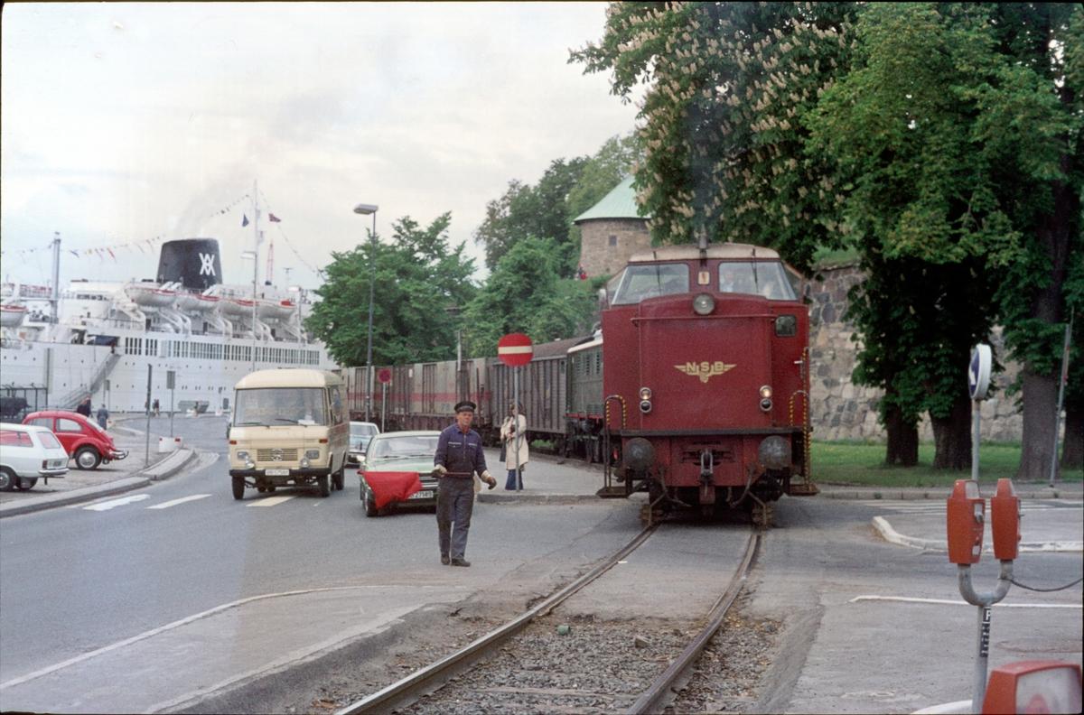 """""""Maler'n"""", godstoget mellom Oslo V og Oslo Ø over Havnebanen med dieselhydraulisk lokomotiv type Di 2 ved Vippetangen. Skiftekonduktøren (malern) viser rødt flagg for biltrafikken. I toget er også El 5 2039, tilhørende Norsk Teknisk Museum."""