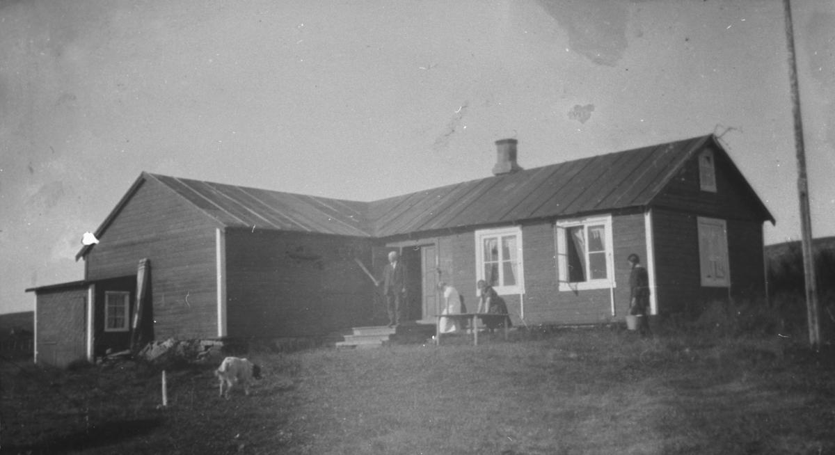 """Familien Hermansen sin hytte """"Støkke"""" fotografert ved Tomaselvaen, Vadsø. På bildet jentene Ingrid Hermansen, Eva og Biddi Hermansen sammen med bestefar. Biddi bærer vann."""