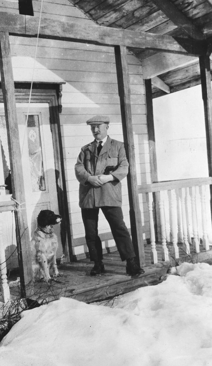 "Vadsø politimester Ludvig Hermansen står på trappa på familiens hytte ""Støkke"" ved Tomaselven i Vadsø påsken 1924. Ved siden av han sitter en jakthund."