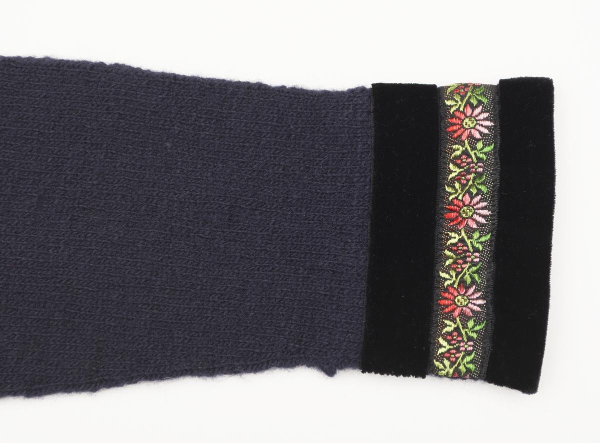 """Mörkblå stickad tröja i Sotenässpunna garnet """"Måseskär"""", kantad i hals och ärmar med först svart sammetsband, ett mönstrat blommigt band (20 mm) och sedan ett svart sammetsband (24 mm) igen. Sammetsbandet i halskanten bredare, vikt in över kanten (27 mm syns). De andra två banden vid halsen går endast på framstycket. Sammetsbandet som kantar ärmarna viks också in (18 mm syns). Mönsterstickat i form av aviga och räta maskor; kant längst ner på tröjan, runt ärmhålen och oket. Ärm- (75 mm) och halskant (60 mm) är skodda med halvlinnetyg. Sprundet bak  stängs i halslinningen med ett hysk/hakpar."""