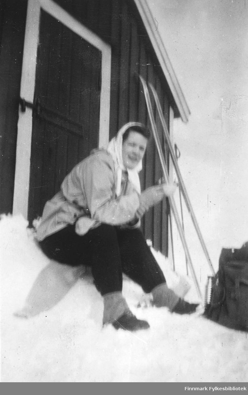 Ragnhild Ebeltoft på skitur, Vadsø-området, 1950-tallet. Her raster hun på ei hyttetrapp. Skiene står stilt opp mot veggen, ryggsekk og termos står i snøen foran henne