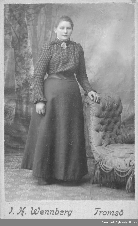 Portrett av ukjent kvinne. Hun er kledd i kjole med rutete overdel. På halsstykket sitter det en brosje, litt samisk eller folkloreinspirert (bunad) i stilen?