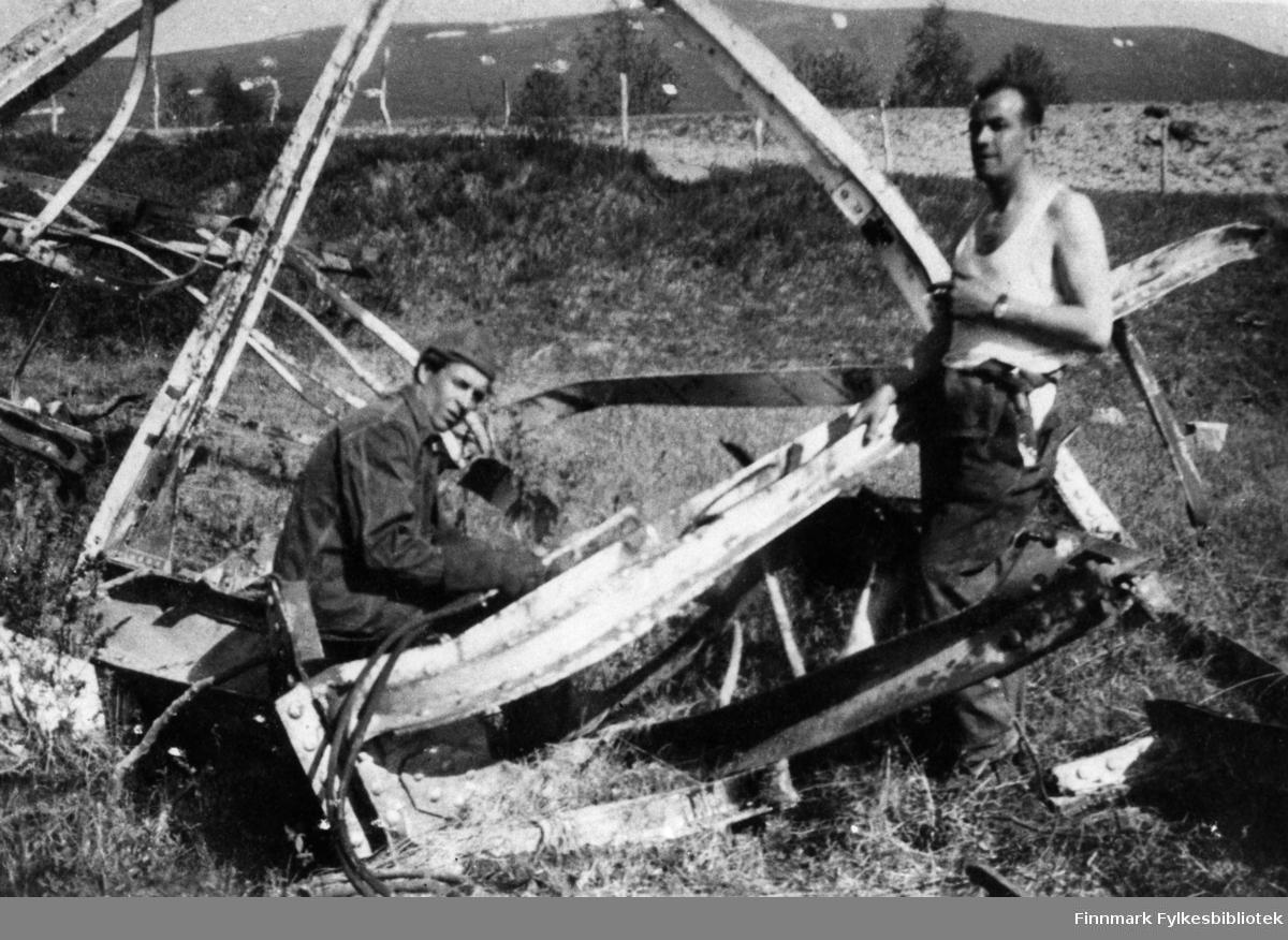 Krigsskadeutbedringer. Portrettfotografi av to menn som henter jernbjelker m.v. fra sprengte bruer.