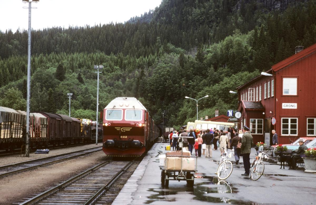 Sørgående dagtog på Nordlandsbanen, hurtigtog 452, kjører inn på Grong stasjon med NSB dieselelektrisk lokomotiv Di 4 652. Reisegods står klart til innlasting, deriblant fotografens sykkel type DBS Golden Flash. Utvendig stasjonsbetjent på plattformen. I spor 3 står godstog 5793 til Bodø.