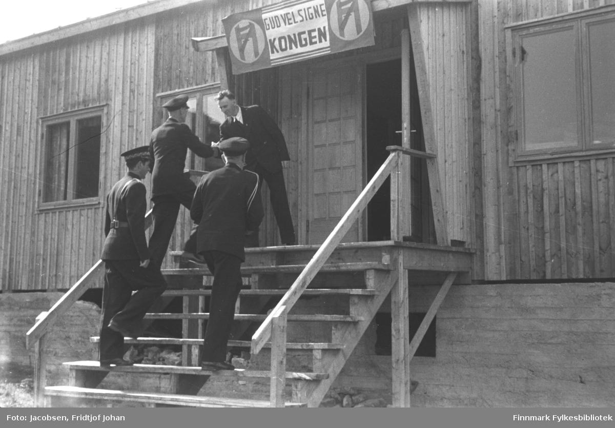 Kongebesøket i Hammerfest 10. juli. De er på vei inn i Frelsesarmeens brakke på Blåsenborg. Bak kongen går fungerende politimester Arvid Dahl. Brakka har en bred trapp opp til inngangen med et lite vindfang rundt. Et banner med Kongenes merke og teksten Gud velsigne Kongen.