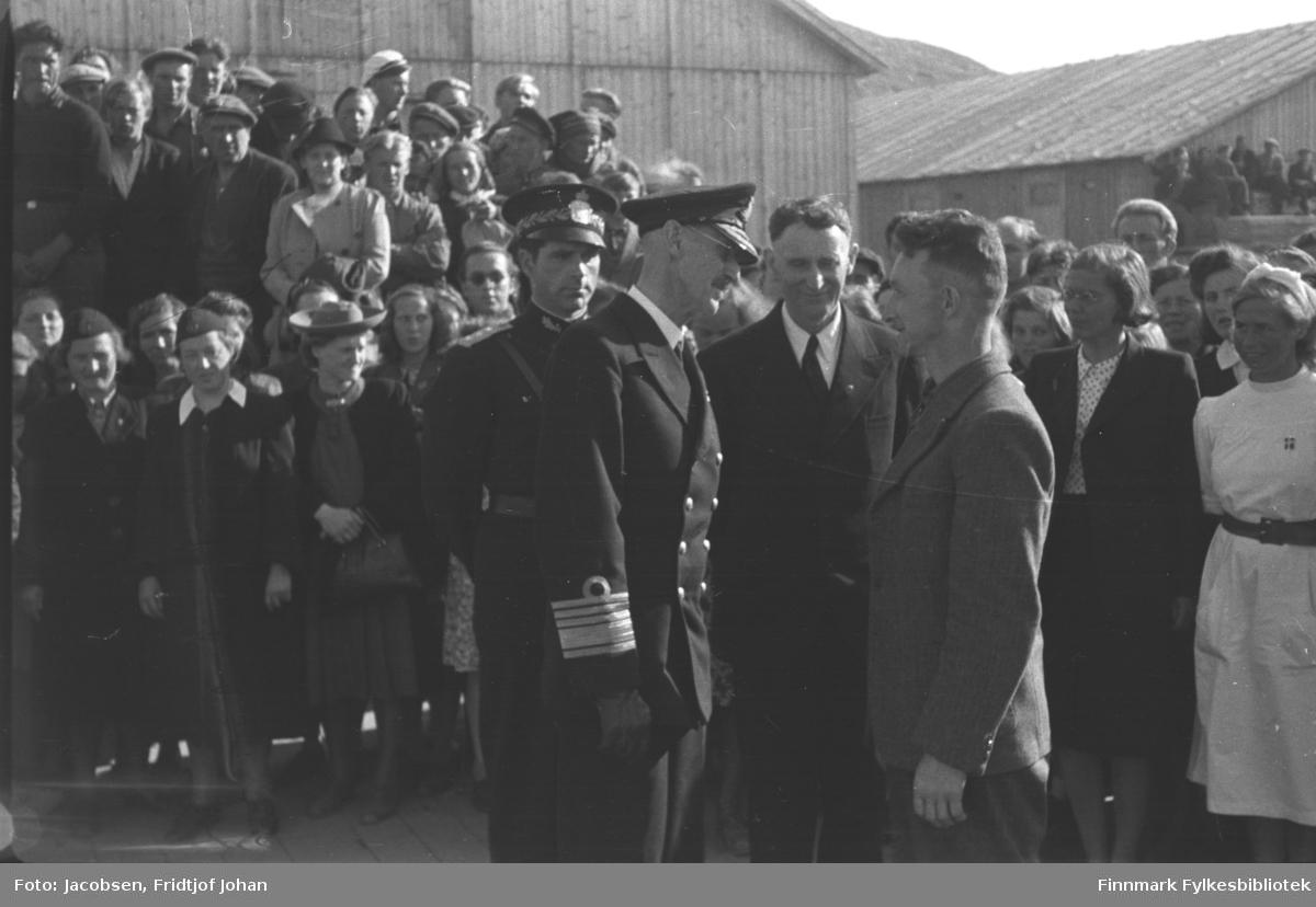 Kongebesøket i Hammerfest 10. juli. Kong Haakon 7 hilser på Tryggve Duklæt. Bak kongen til venstre står politimester Arvid Dahl. Mellom Kongen og Duklæt står ordfører Albrigtsen. En ganske stor folkemengde står rundt dem og et par store brakker ses i bakgrunnen