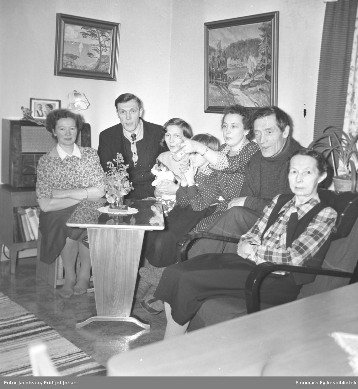 Gruppeportrett av medlemmer av familien Nakken/Jacobsen. Fra venstre: Malene Nakken, Dagfinn Nakken, Synnøve Nakken, Arne  Jacobsen, Aase Randi Jacobsen, Arne Nakken og Sigrid Nakken. Folkene sitter i en stue og er ganske pent kledt. Et lite stuebord med en blomsterdekorasjon oppå, står foran dem. Et par malerier henger på beggene og langs veggen står et radiobord med en stor radio oppå.