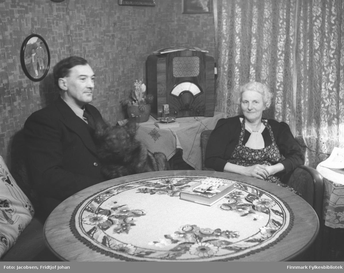 Frithjof Jacobsen, farfar til Arne Jacobsen, sitter med en hund på fanget. Ved siden av sitter hans kone og Arnes farmor, Olga Josefine Jacobsen. Han har mørk dress på og Olga har mønstret kjole med mørk jakke. Et stort, rundt bord med en lys, mønstret duk står foran dem og en bok ligger oppå. Tykke gardiner henger foran vinduet og et bord står i hjørnet med en radio oppå. Flere innrammede fotografier henger på veggene.
