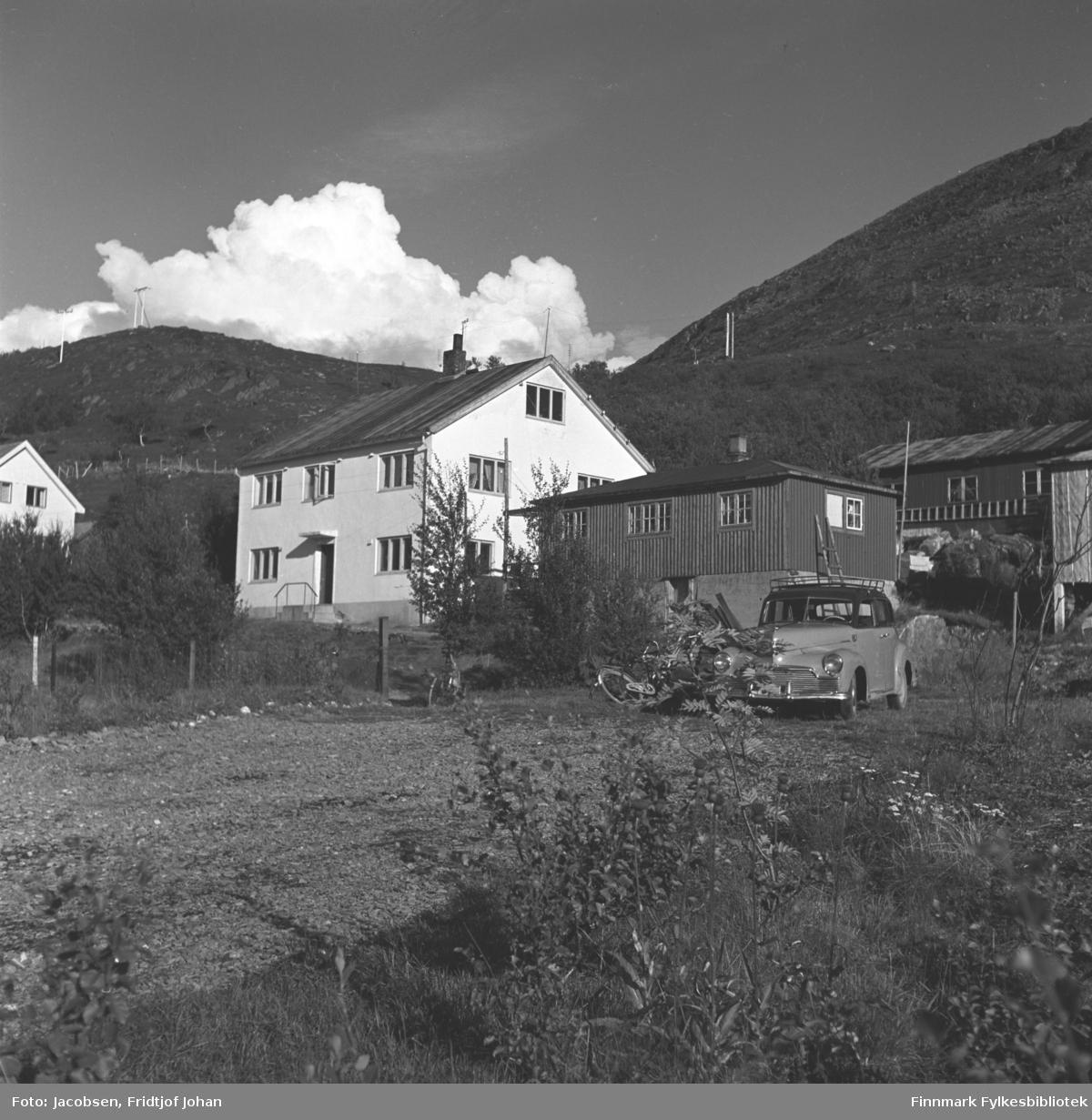 Huset til Arne Nakken, Fridtjof Jacobsens svigerfar i Bjørkåsen i Rypefjord. Huset er stort og hvitmalt med mange tre-delte vinduer. Hytta ved siden av tilhørte Aase og Fridtjof. En bil og to sykler står i enden av den grusdekte oppkjørselen. En del løvtrær og små busker står på omårdet og i hagen. Røstveggen på en annen bolig ses helt til venstre på bildet og en liten hytte til høyre. Flere el-stolper står i fjellsiden.