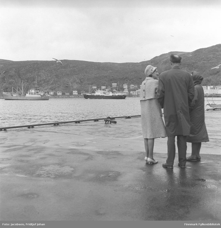 Fra kaia i Hammerfest en augustdag i 1964. Tre personer står og ser når Hurtigruta er på tur ut fra havna. Den ukjente damen som står til venstre på bildet har lyse klær, hatt og sko. Ved siden av henne står Alf Edvard Jacobsen. Han har mørke bukser og en mørk frakk på seg. Til høyre står Aase Jacobsen. Hun er iført en mørk kåpe med hette. Et lavt metallrekkverk står langs kaikanten og ute på havna ligger et stor skip. Husene står langs Fuglenesveien og på Hamran. Helt til høyre på bildet, under Mollafjell, står Hauans materialhandel. Et par måker flyr over kaia. Skipene på havna er M/S Guttorm Jarl (til venstre) og hurtigruteskipet M/S Barøy.