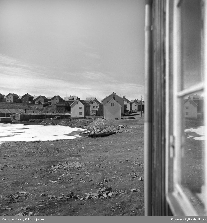 Utsikt fra stuevinduet til Fridtjof Jacobsen i Storvannsveien. Husene oppe til venstre på bildet er Moreneveien og området der brakkene står ble kalt for Belsen. Husene midt på bildet er Storvannsveien. Noen el-stolper står langs den grusdekte Storvannsveien og flere stolper ligger i veikanten, klar til å settes opp. Storvannet er islagt, men terrenget rundt er bart så bildet er nok tatt en vårdag.