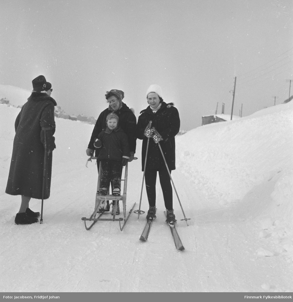 Fire personer på tur en vinterdag med mye snø i terrenget. Til venstre på bildet står Olga Jacobsen. Hun har en mørk kåpe, mørk hatt, mørke sko og har en krykke i sin høyre arm. I midten står Karen Trondsen med spark. Hun har en mørk jakke og lue på seg. På sparken står en gutt i mørke klær og topplue på hodet. Dette kan være sønnen hennes, Kjell Edvard. Til høyre står Judith Hartviksen med ski på beina og skistaver i hendene. Hun har mørk bukse og mørk anorakk, hvit lue og votter på hendene. Noen bygg og el-stolper ses i bakgrunnen.