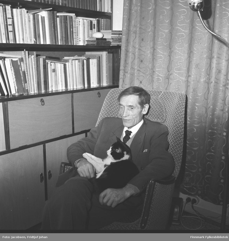 Arne Nakken med en katt på fanget hjemme i stua til Fridtjof og Aase Jacobsen. Han sitter i en lenestol og har en mørk dress med hvit skjorte og slips på seg. Bak han henger mørke, mønstrete gardiner. Ved siden av han står en veggseksjon. Seksjonen har flere skap og hyller. Hyllene er full av bøker og en stålampe ses oppe til høyre på bildet. Fotografiet er sannsynligvis tatt på julaften.