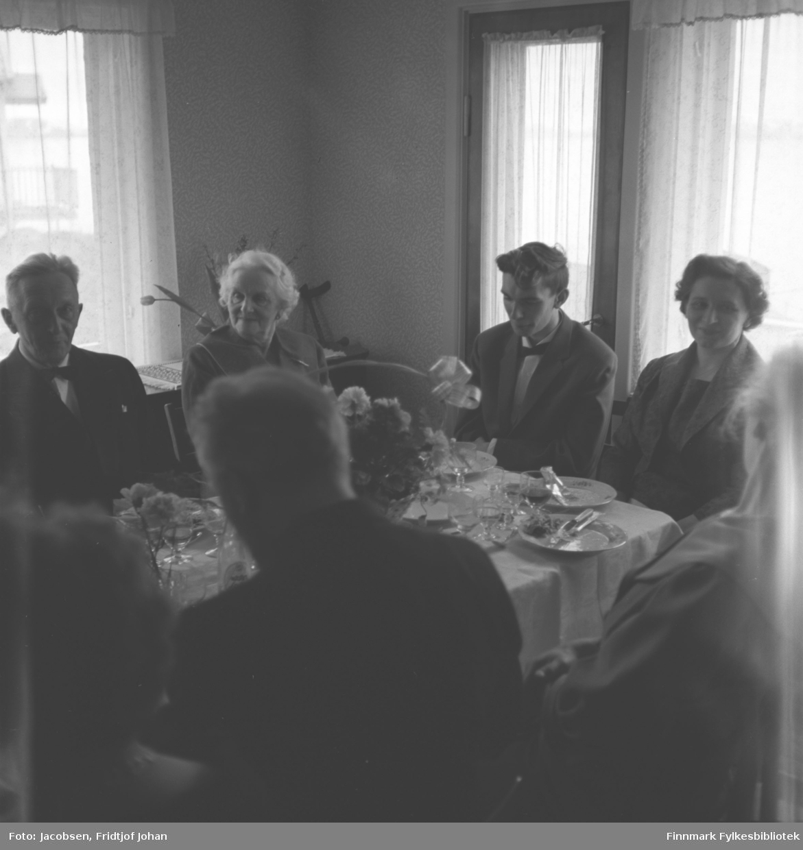 Fra Åge Christian Jacobsens konfirmasjon 8. mai 1960. Bak fra venstre sitter Paul Sørensen. Han har en mørk dress med hvit skjorte og sløyfe på seg. Olga Jacobsen sitter ved siden av han og er iført en mørk overdel. Ved enden av bordet sitter Åge Christian i mørk dress med hvit skjorte og sløyfe. Ved siden av han sitter moren hans, Alfhild Marie Jacobsen iført en mørk kjole. Noe diffust til høyre på bildet sitter Ingeborg Jacobsen. Foran med ryggen til fra venstre sitter Karl Johan Sørensen. Bordet er dekket med kopper, glass, fat, bestikk og en blomsterdekorasjon som står oppå en hvit duk. Tynne gardiner henger foran vinduene og balkongdøra.