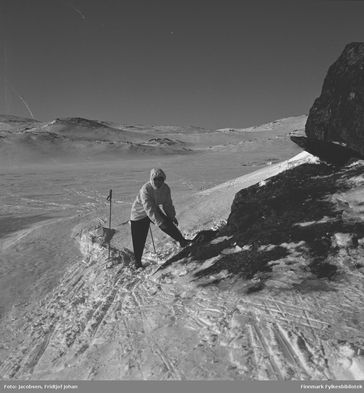 Aase Jacobsen på skitur. Hun har mørk bukse og lys anorakk med hette på seg. Skistavene hennes står i snøen rett bak henne. Terrenget er snødekt, men noen steiner/berg stikker gjennom snøen. Det er skispor over deler av området og skyfri himmel.