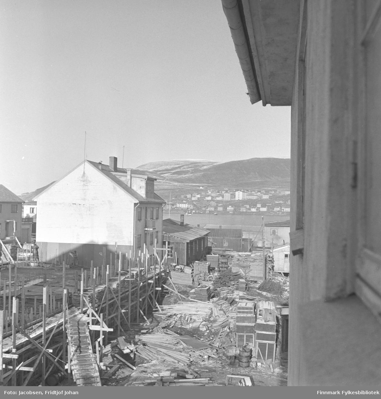 Dette bildet er tatt fra Fridtjof Jacobsens kontorvindu. Huset som bygges til venstre er politihuset. Det store bygget helt bak i bildet er Hammerfest sykehus. Hus nummer tre fra høyre (medregnet Fridtjofs kontorbygg) er Norges Bank